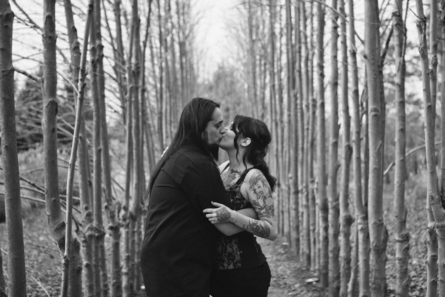 couple kisses in a row of trees during their engagement session with their wedding photographer for sculpture in hamilton nj