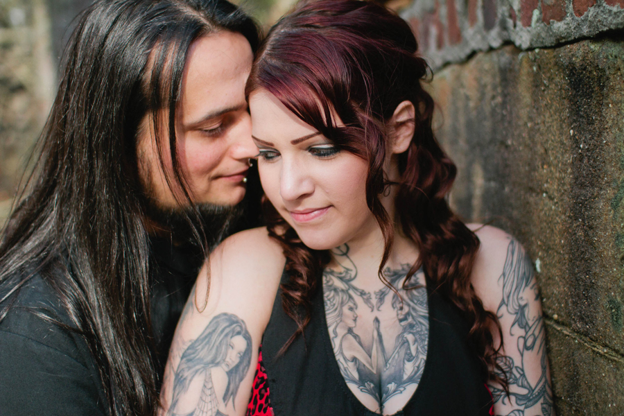 tattooed couple poses for engagement photos for markow photography at an abandoned site