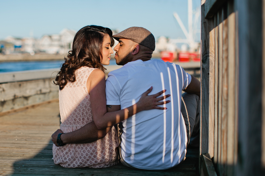 Couple kisses on the boardwalk at Point Pleasant inlet during their engagement photo session with their monmouth county nj wedding photographers markow photography