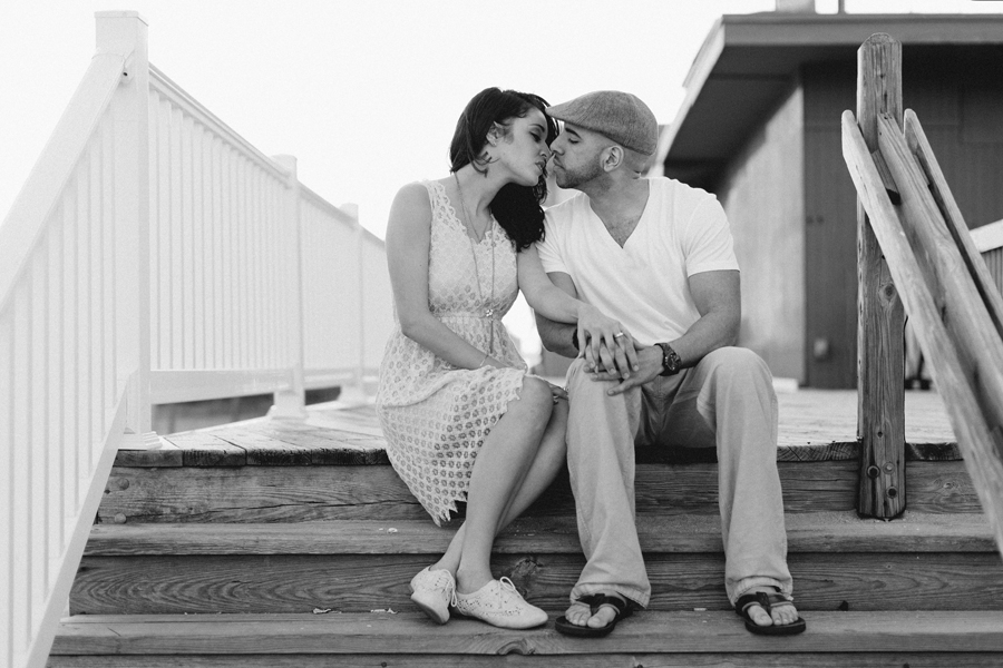 Couple kisses at Point Pleasant inlet during their engagement photo session with their monmouth county nj wedding photographers markow photography