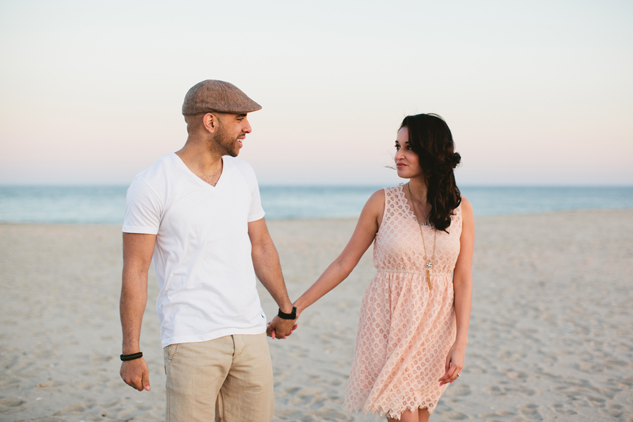 Couple walks on the beach together at Point Pleasant during their engagement photo session with monmouth county nj wedding photographers markow photography