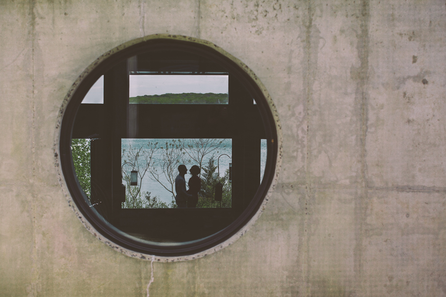 couple embraces through window at the manasquan reservoir during their engagement photo session with their monmouth county nj wedding photographers julianne and steven of markow photography