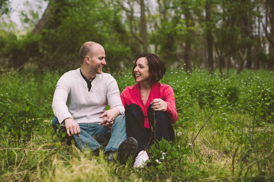 couple laughs while sitting in the woods at the manasquan reservoir during their engagement photo session with their monmouth county nj wedding photographers julianne and steven of markow photography