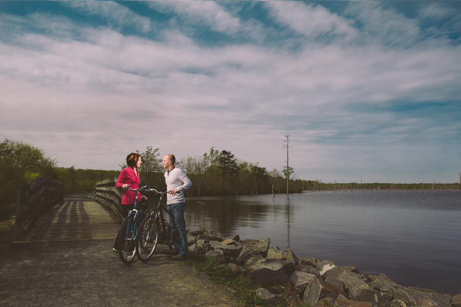 couple poses with their bikes at the manasquan reservoir during their engagement photo session with their monmouth county nj wedding photographers julianne and steven of markow photography