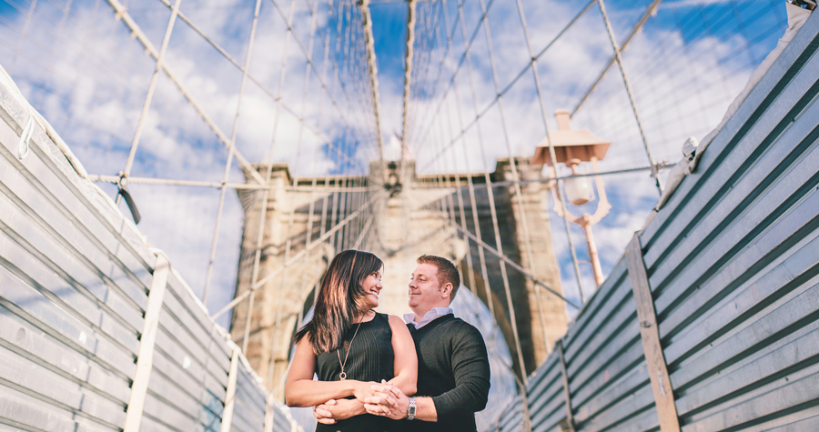 couple poses on brooklyn bridge during their engagement photo session with nyc wedding photographers