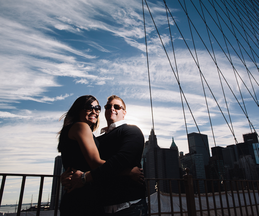 couple on brookyln bridge for engagement photo session with nyc wedding photographers
