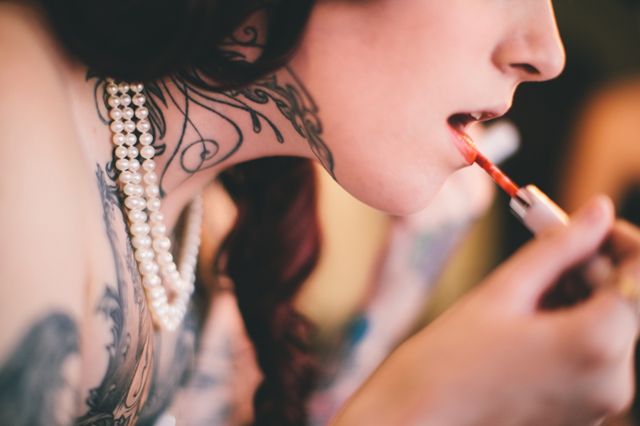 bride with neck tattoo putting on makeup